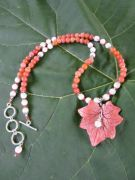 Coppery colored Cineraria leaf on red aventurine with shell, red crystal and sterling silver